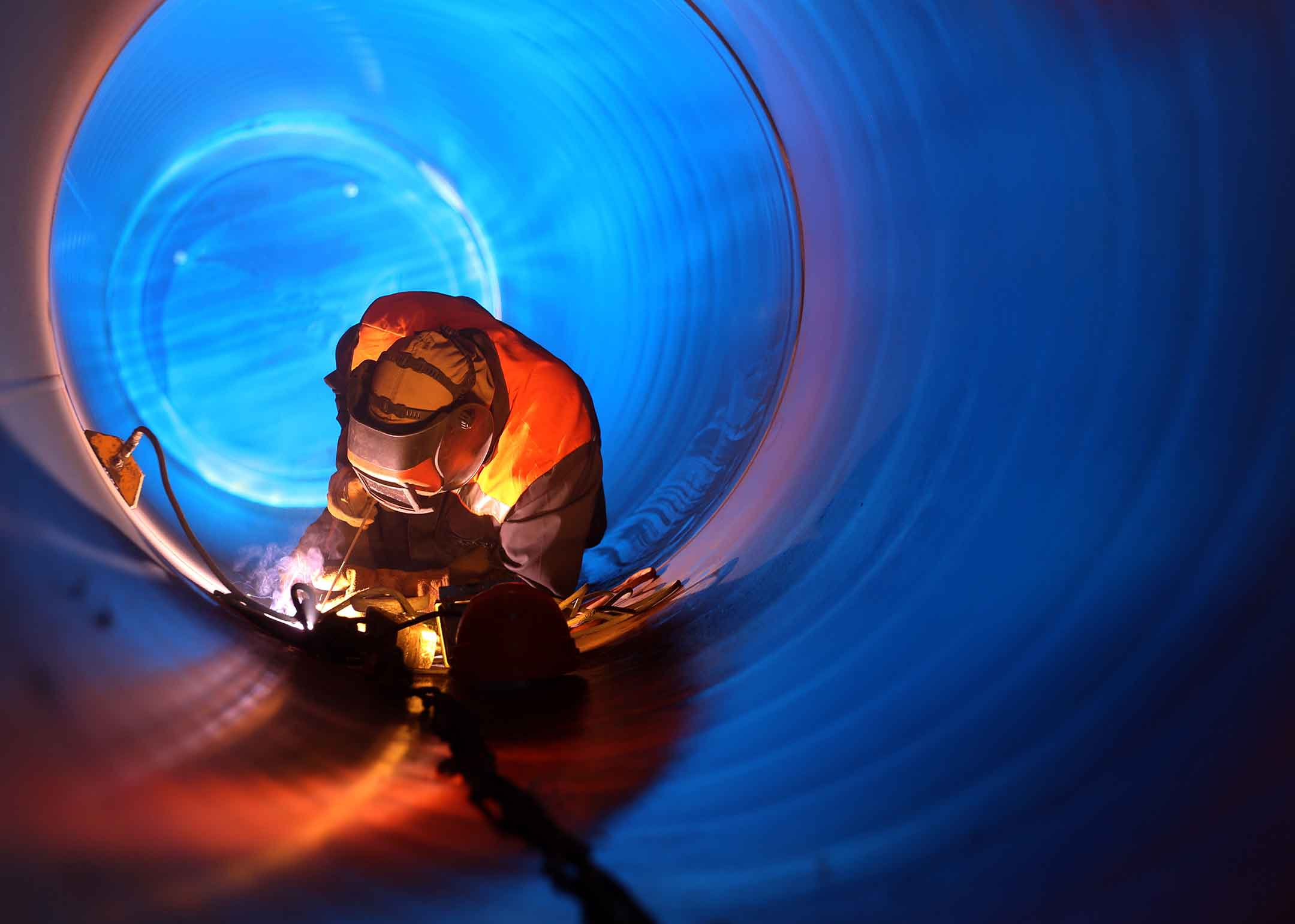 A person welding in a large pipe