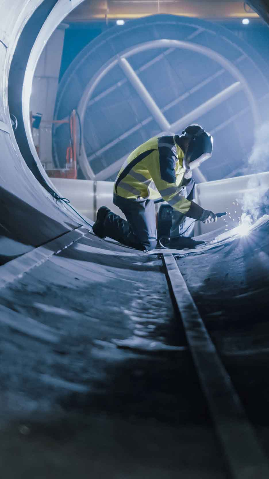 Person welding in a large pipe