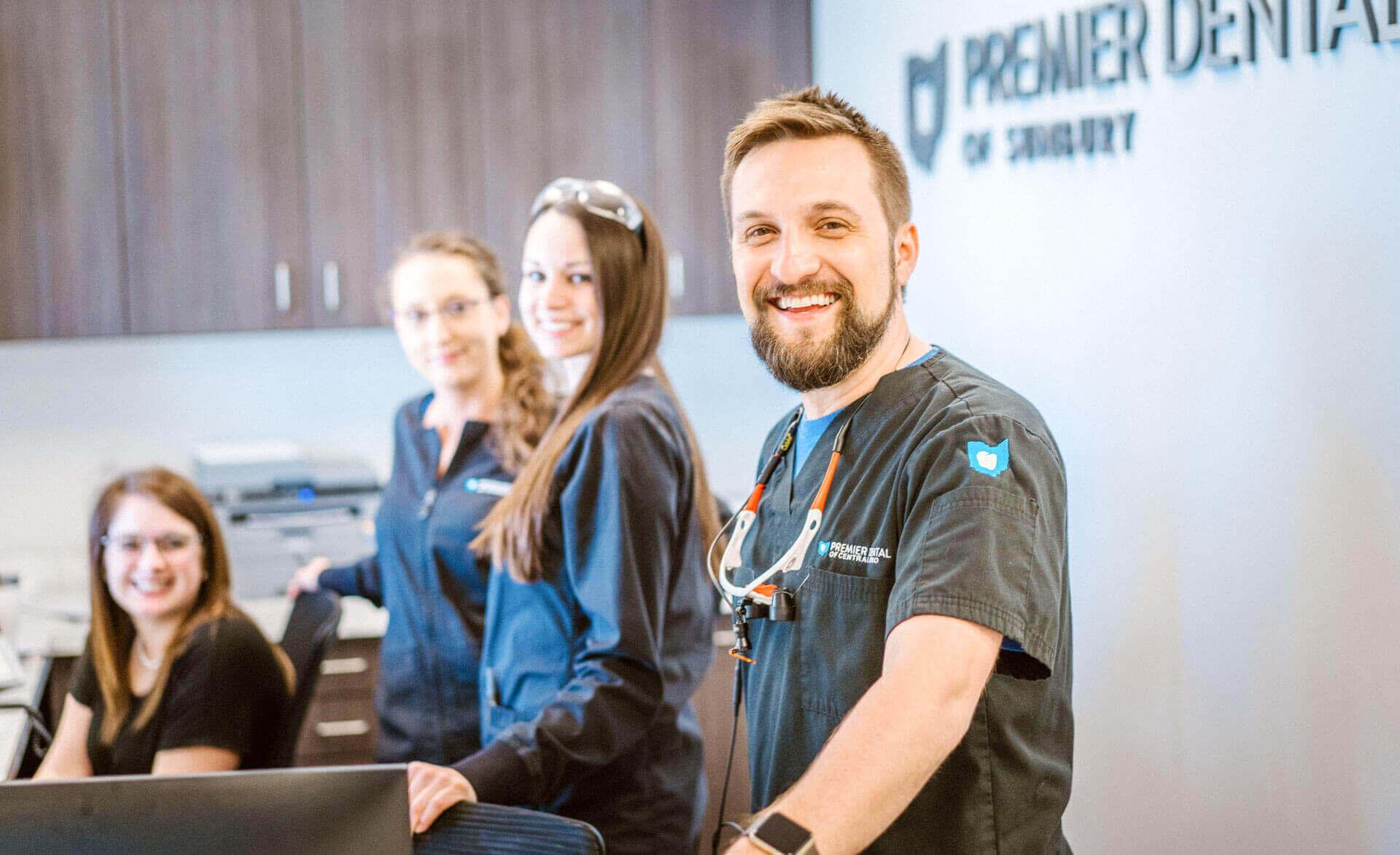 Dr. Doug Hudoba and his dental team at the front desk of Premier Dental of Sunbury