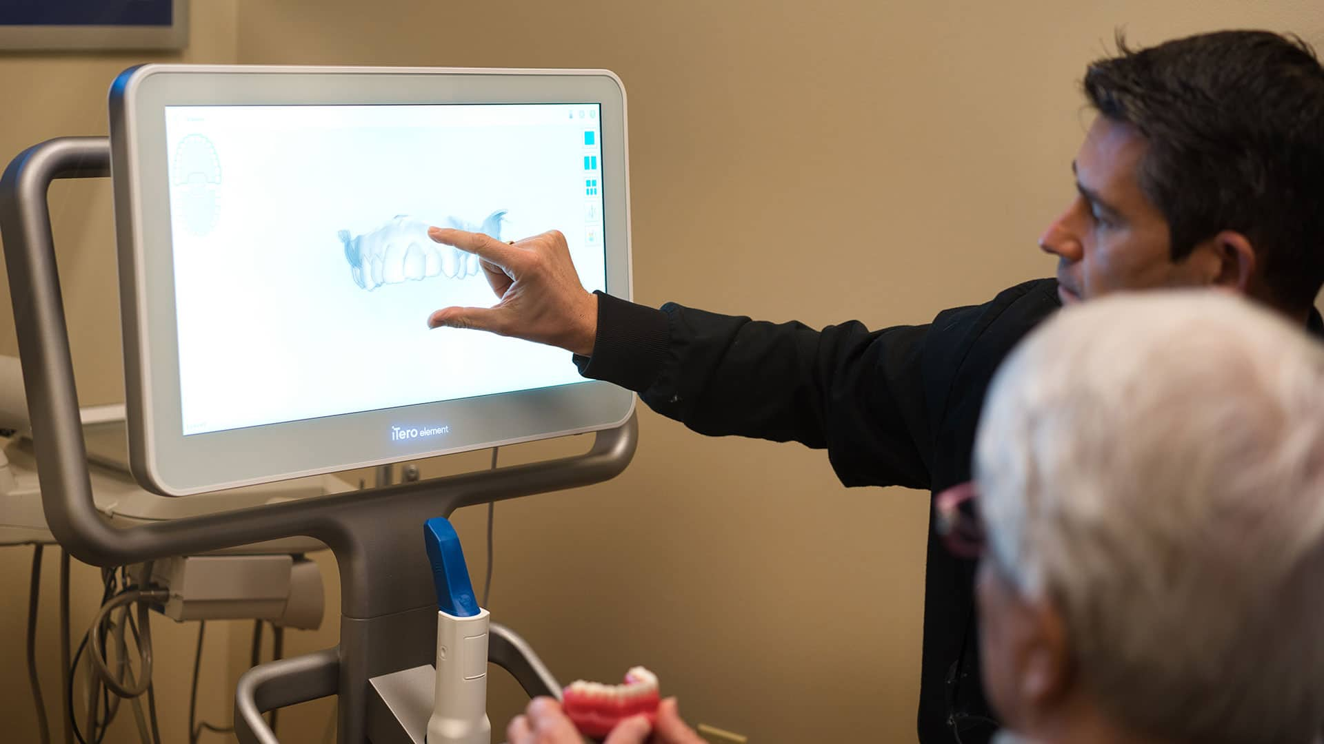 A dentist at Premier Dental of Ohio showing the results of the iTero digital scanner