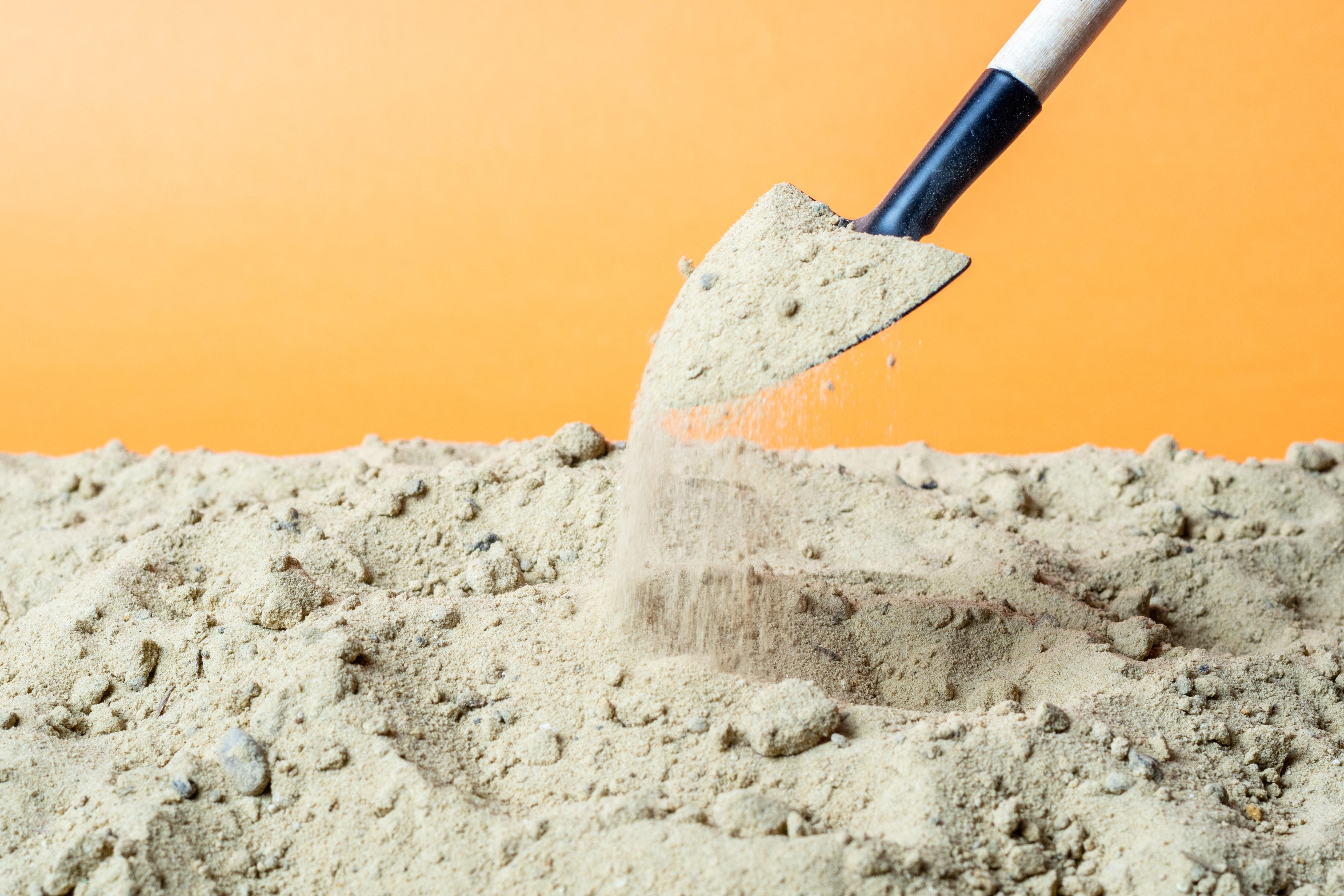 shovel picking up sand against an orange background