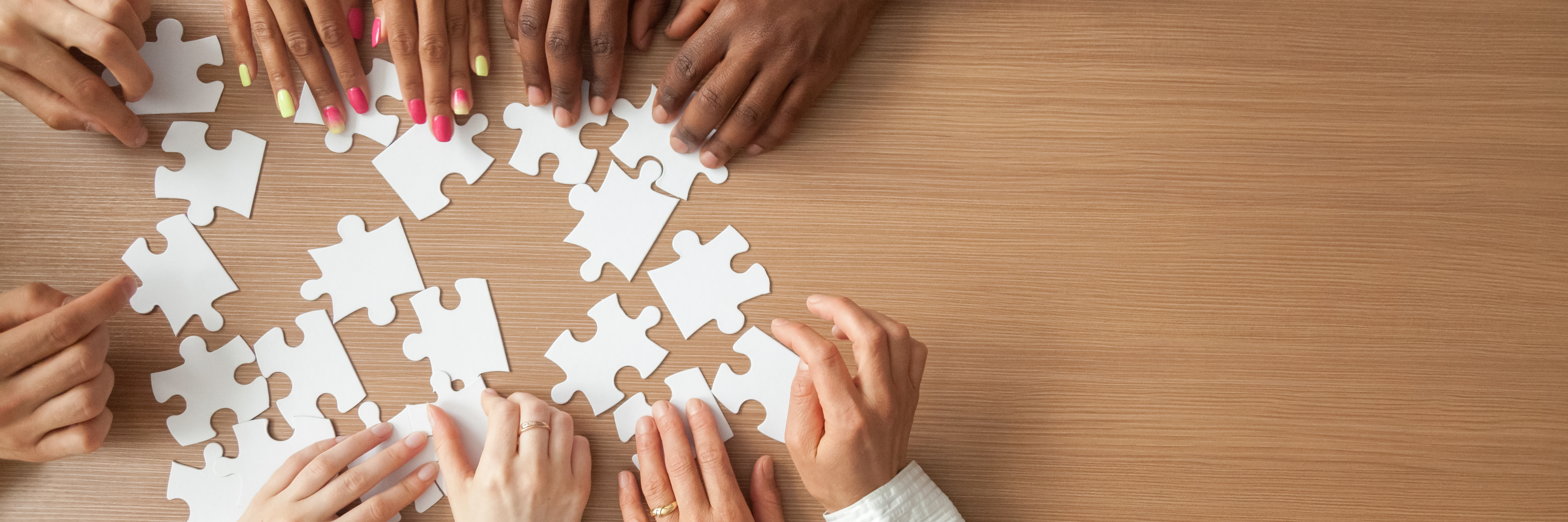 people's hands assembling a puzzle together on a wooden table