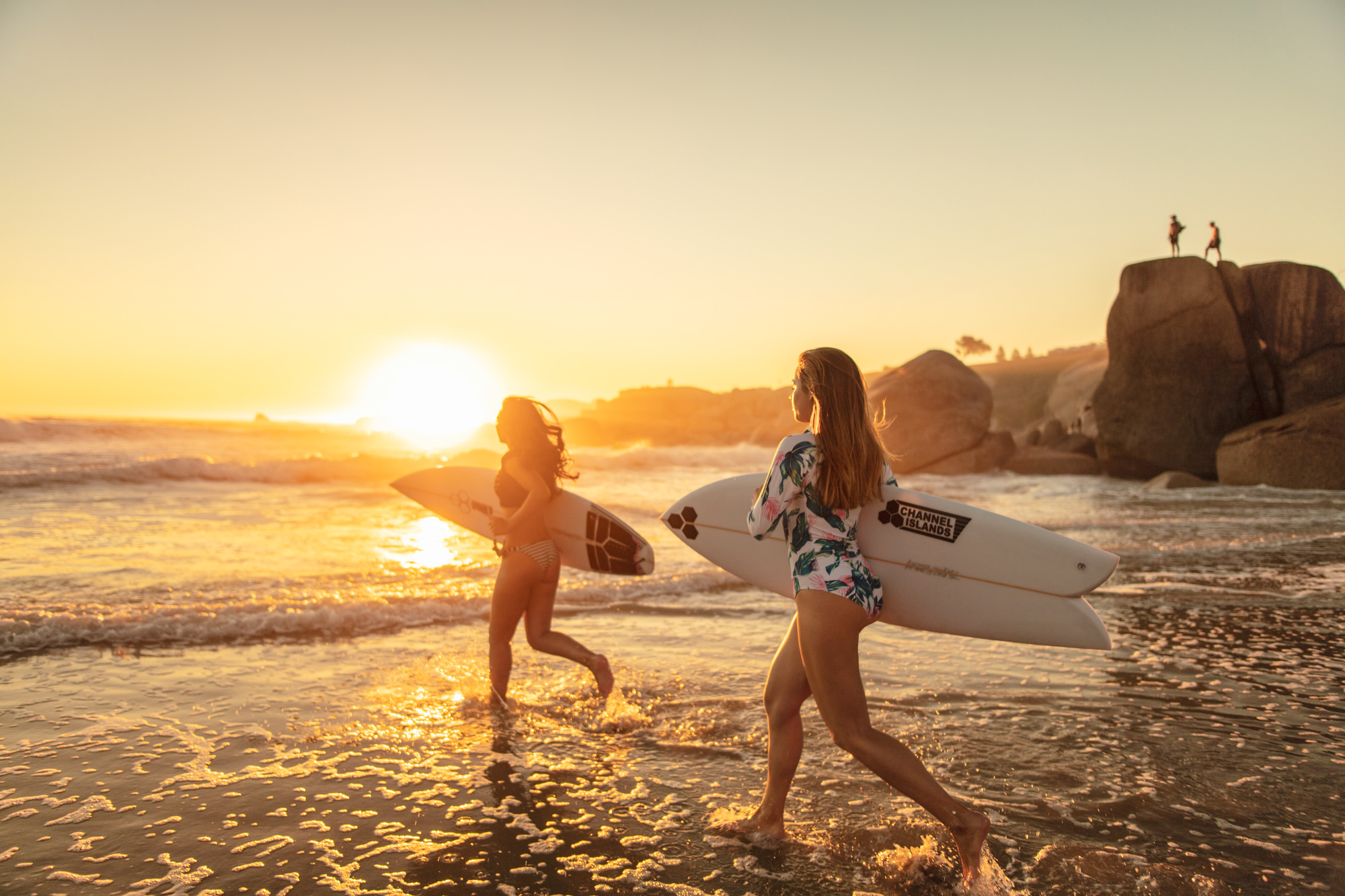 Image of girl friends running into the ocean for a sunset surf in Cape Town for Tsogo Sun's Image Library & Content Library by Michelle Wastie Photography