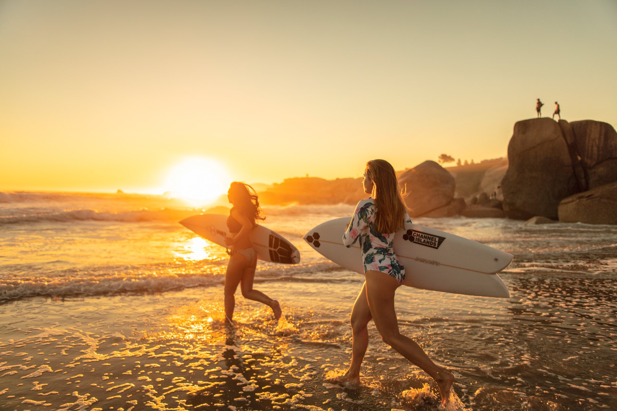 Image of girls running on the beach to the water for a sunset surf in Cape Town for  Tsogo Sun's Image Library & Content Library by Michelle Wastie Photography