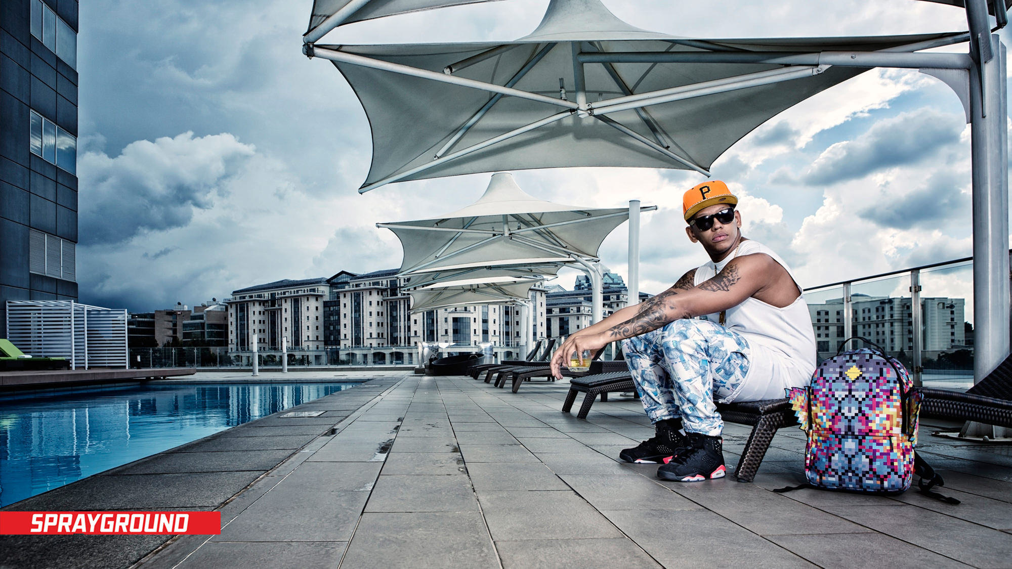 Image of Da L.E.S on Sandton Rooftop by pool for Sprayground's Africa Launch by Michelle Wastie Photography.