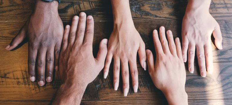 Different people's hands placed on a table
