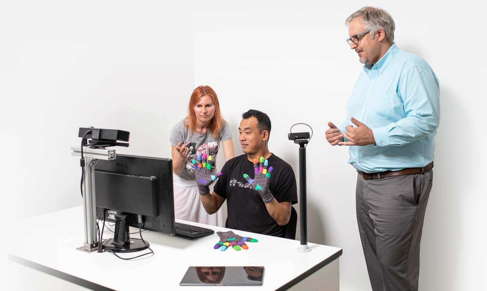 A white woman, a man of color,and a white man look on a computer screen and discuss what they see. Man of color is signing  in special signing gloves