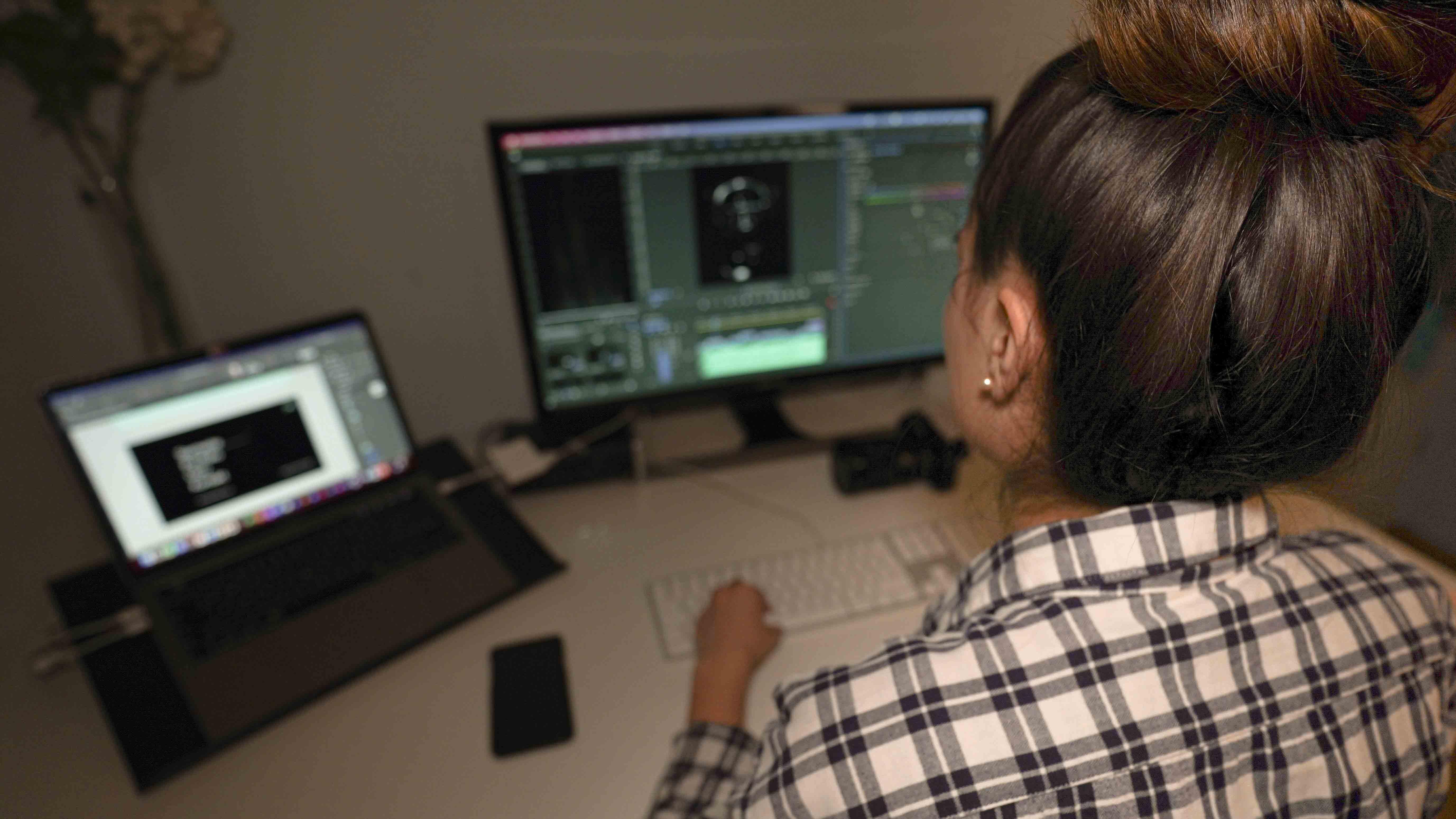 Post-Production: Multimedia Produzentin bearbeitet ein Video.