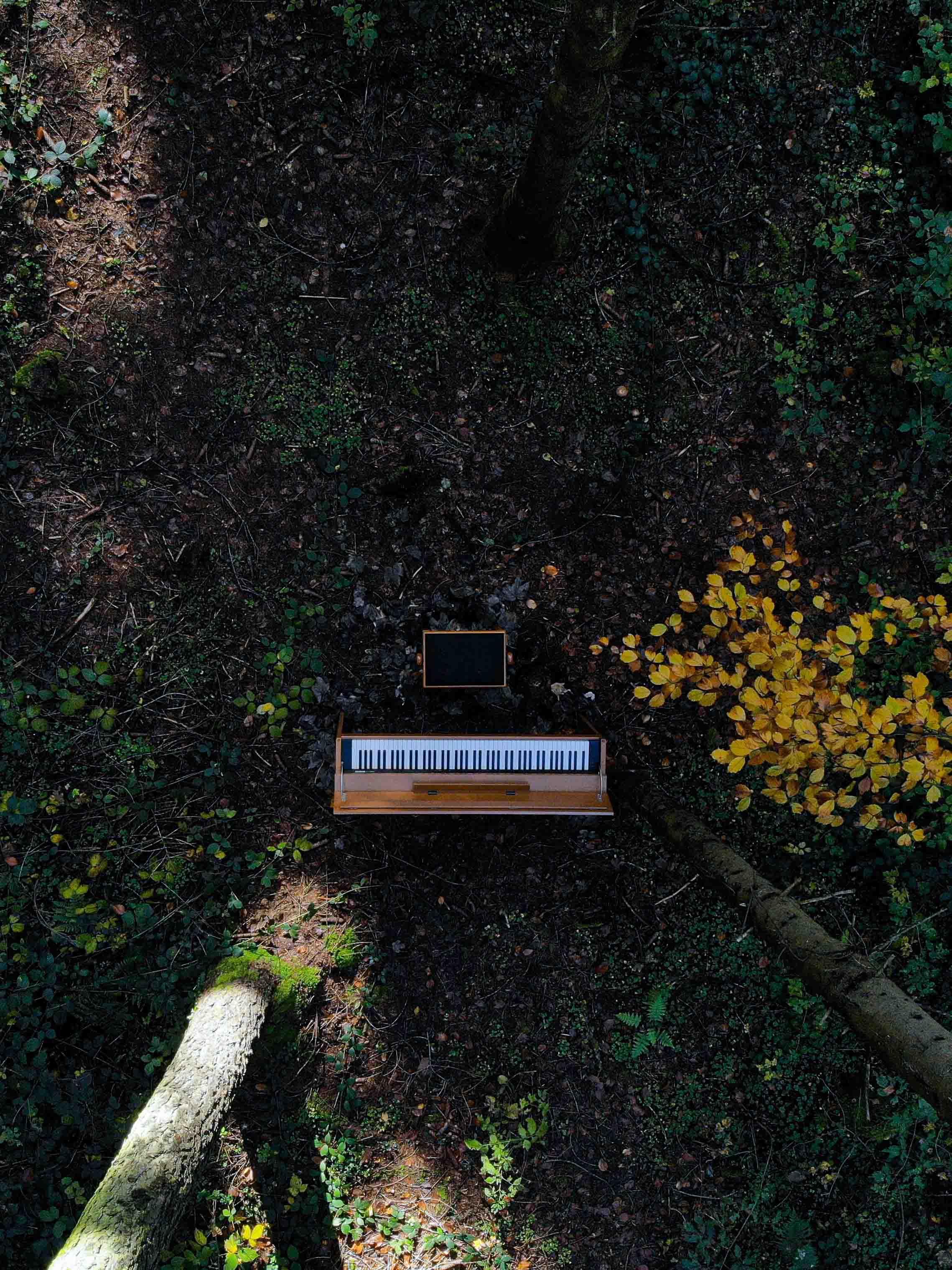 Drohnenaufnahme von einem Klavier im Wald.