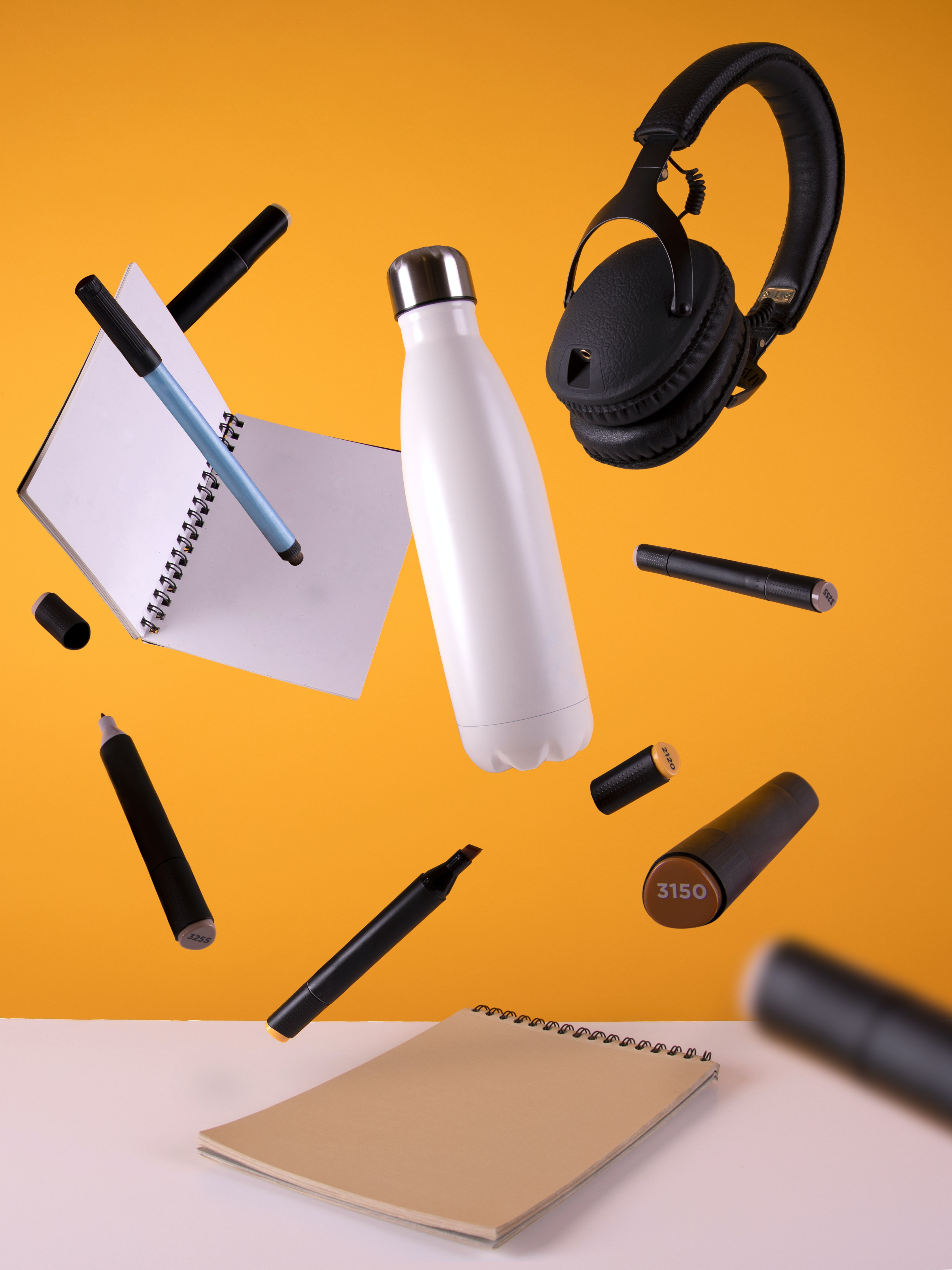 Image Credit - KOBU Agency via Unsplash. Image of floating pens, sketchbooks and headphones with a yellow background