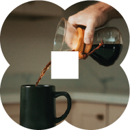 An image of a person pouring black coffee from a pitcher into a large mug