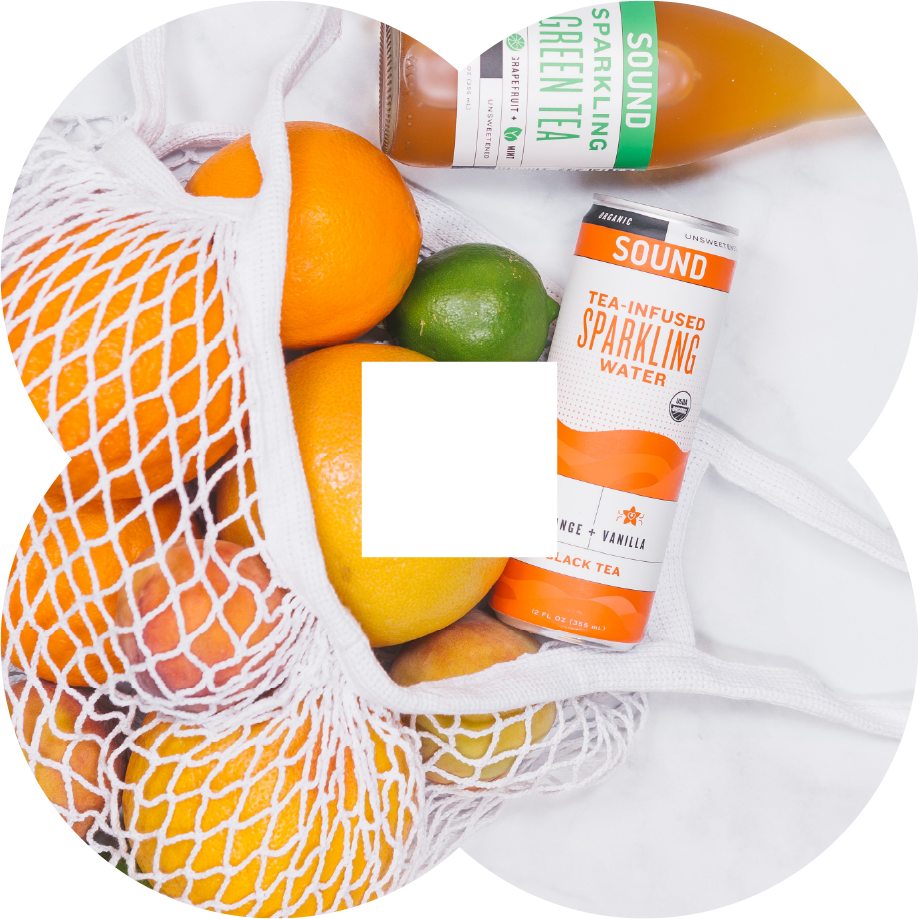 Citrus fruits and soft drinks in a white mesh bag.
