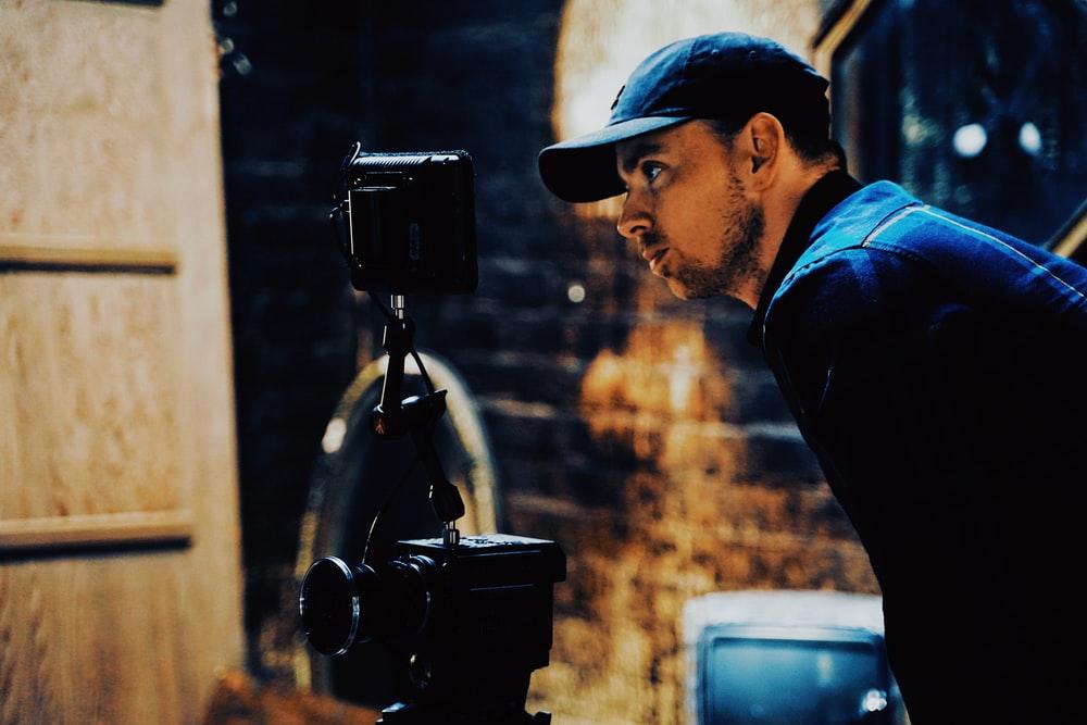man in blue shirt and black cap holding black camera