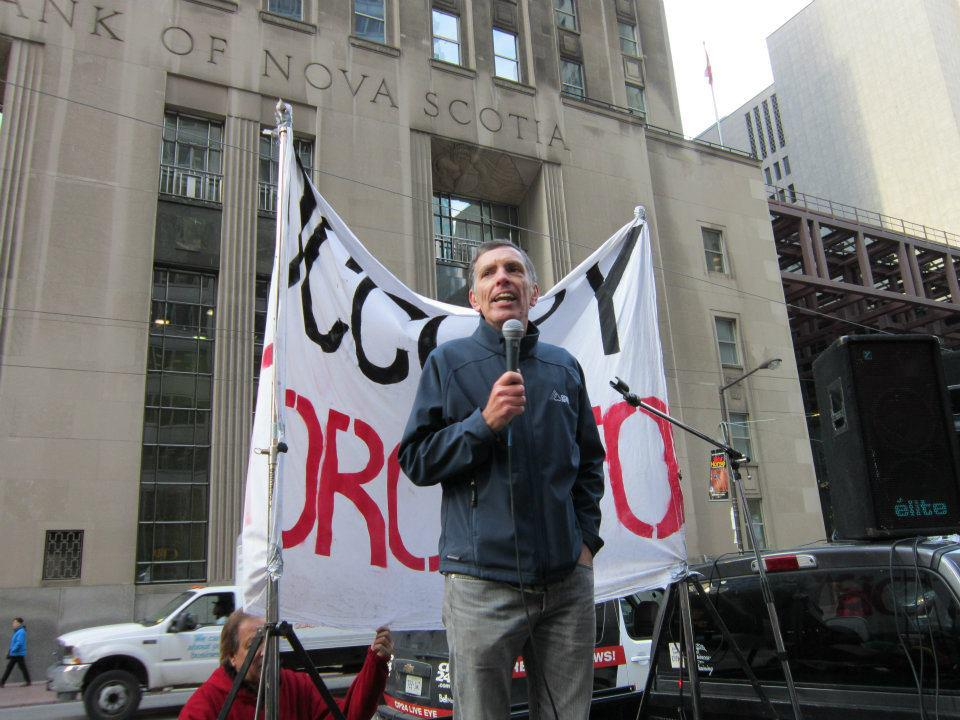 David McNally stands in front of an Occupy Toronto banner, addressing a rally
