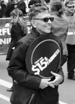 David McNally carrying a sign at a Fight for 15 march