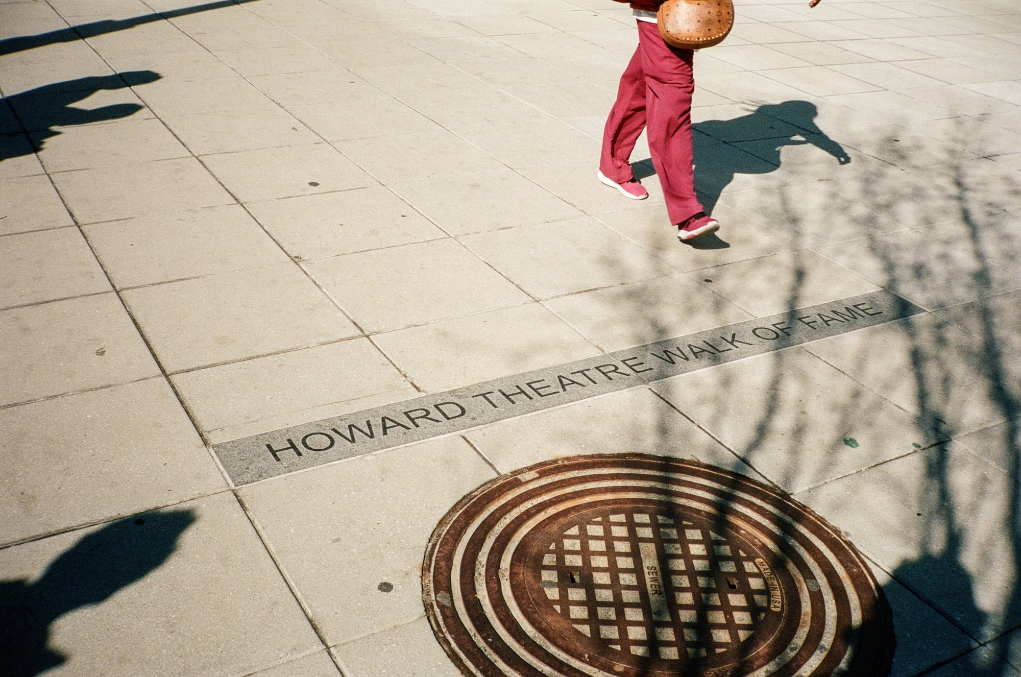 """Person walking on granite threshold, which reads """"Howard Theatre Walk of Fame"""" in sidewalk on 7th Street NW in DC."""