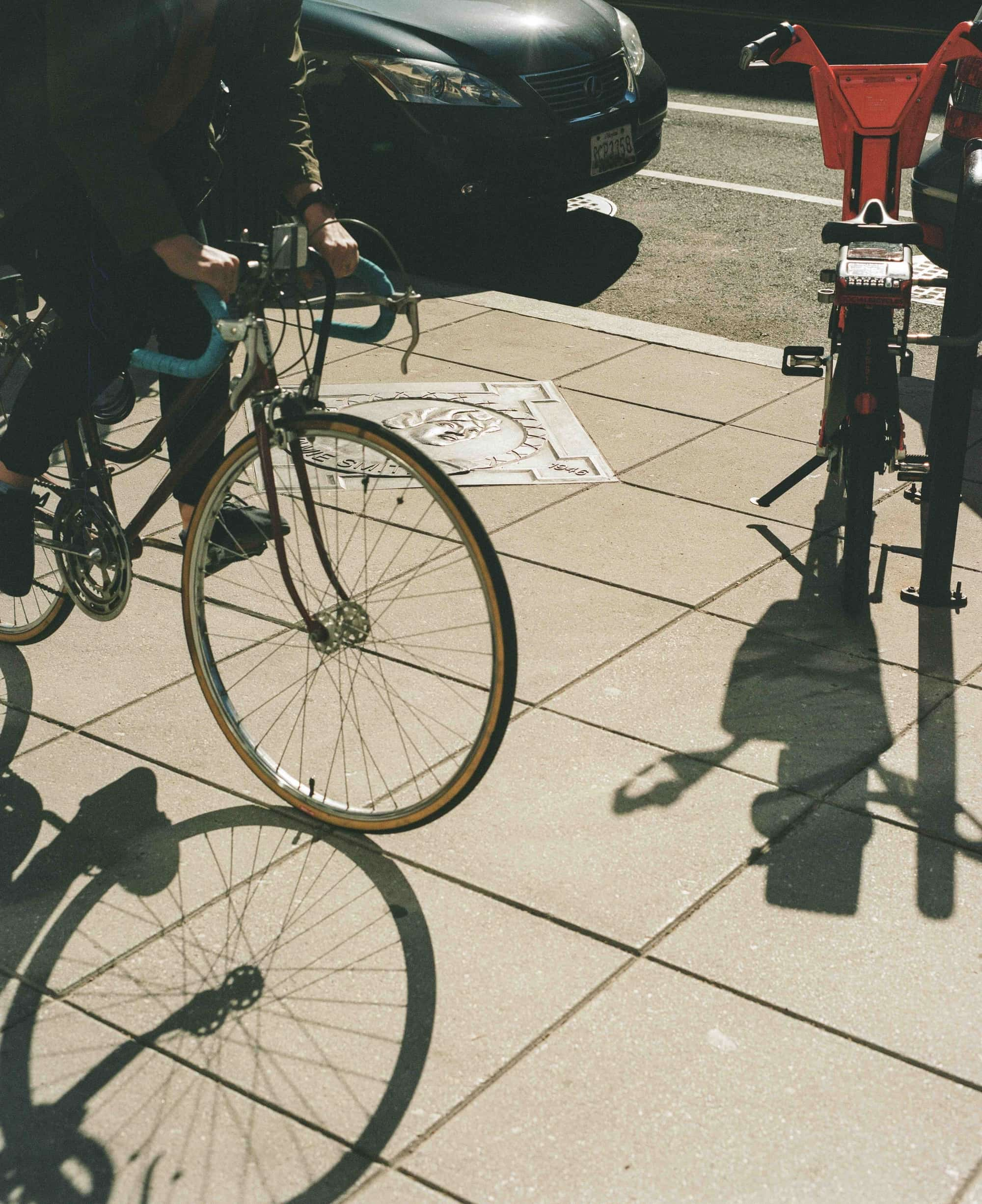 Person riding bicycle by Howard Theatre Walk of Fame medallion on sidewalk on 7th Street NW in DC.