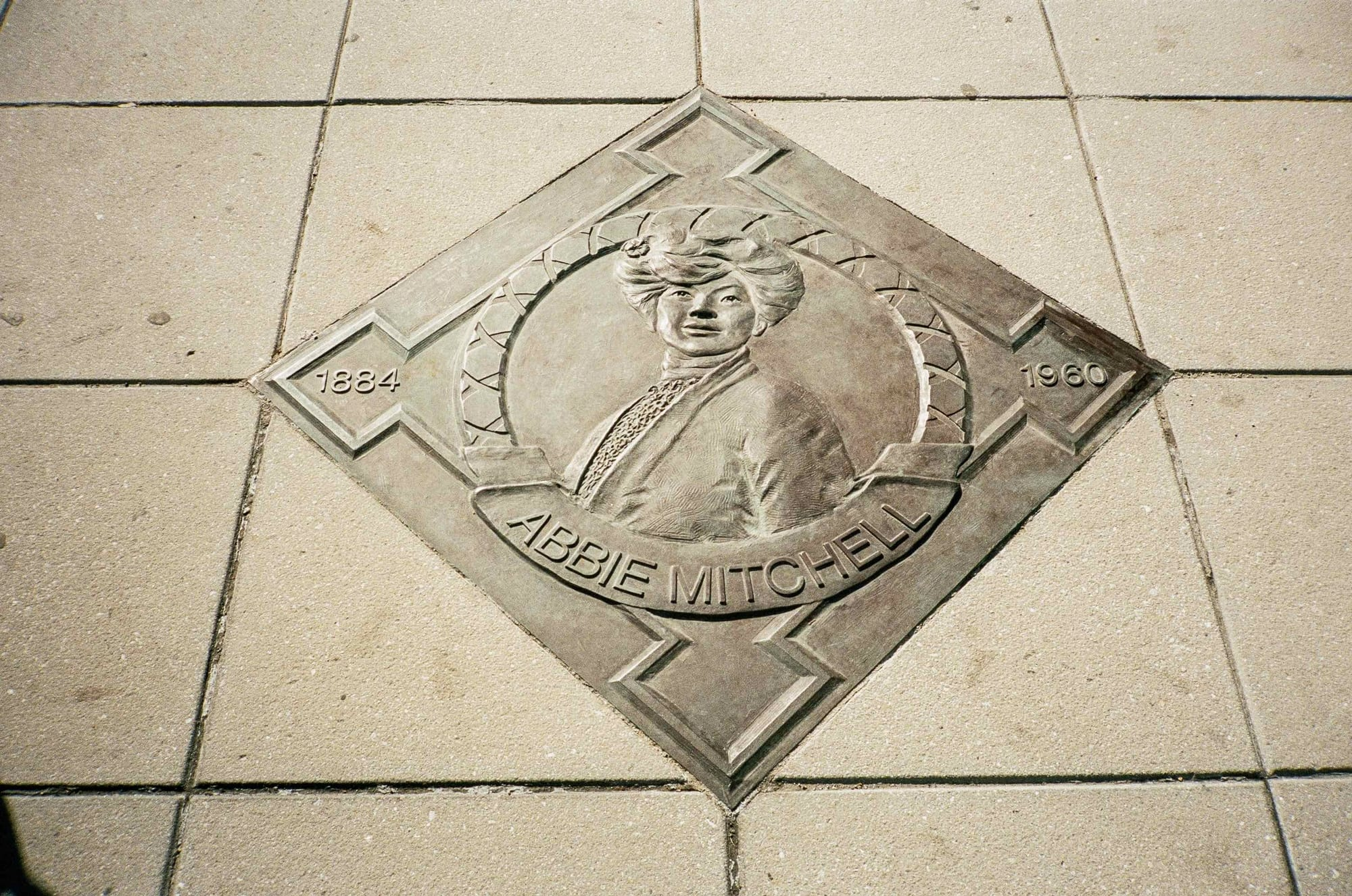 Howard Theatre Walk of Fame medallion in sidewalk, showing bas relief image of Abbie Mitchell in bronze.