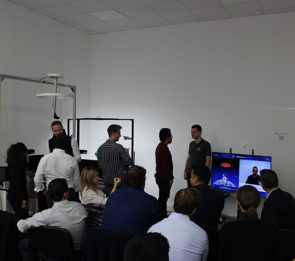 A group of people are watching a SignAll Learn game on a wide screen