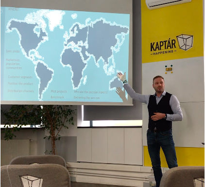 A man is making a presentation,standing near a world map
