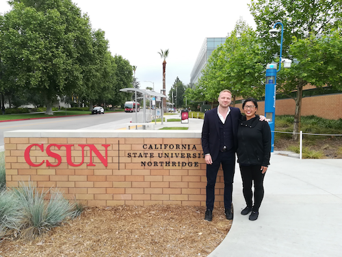 Man and woman standing in front of the sign of CSUN