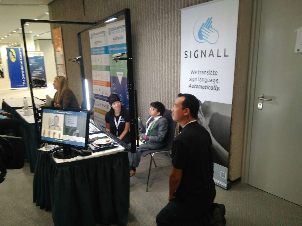 SignAll booth. A person is practicing, two people from SignAll team are around