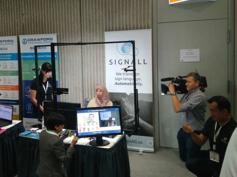 A POC female lady in hijab is practicing ASL with SignAll Learn system. A video operator is filming her from aside