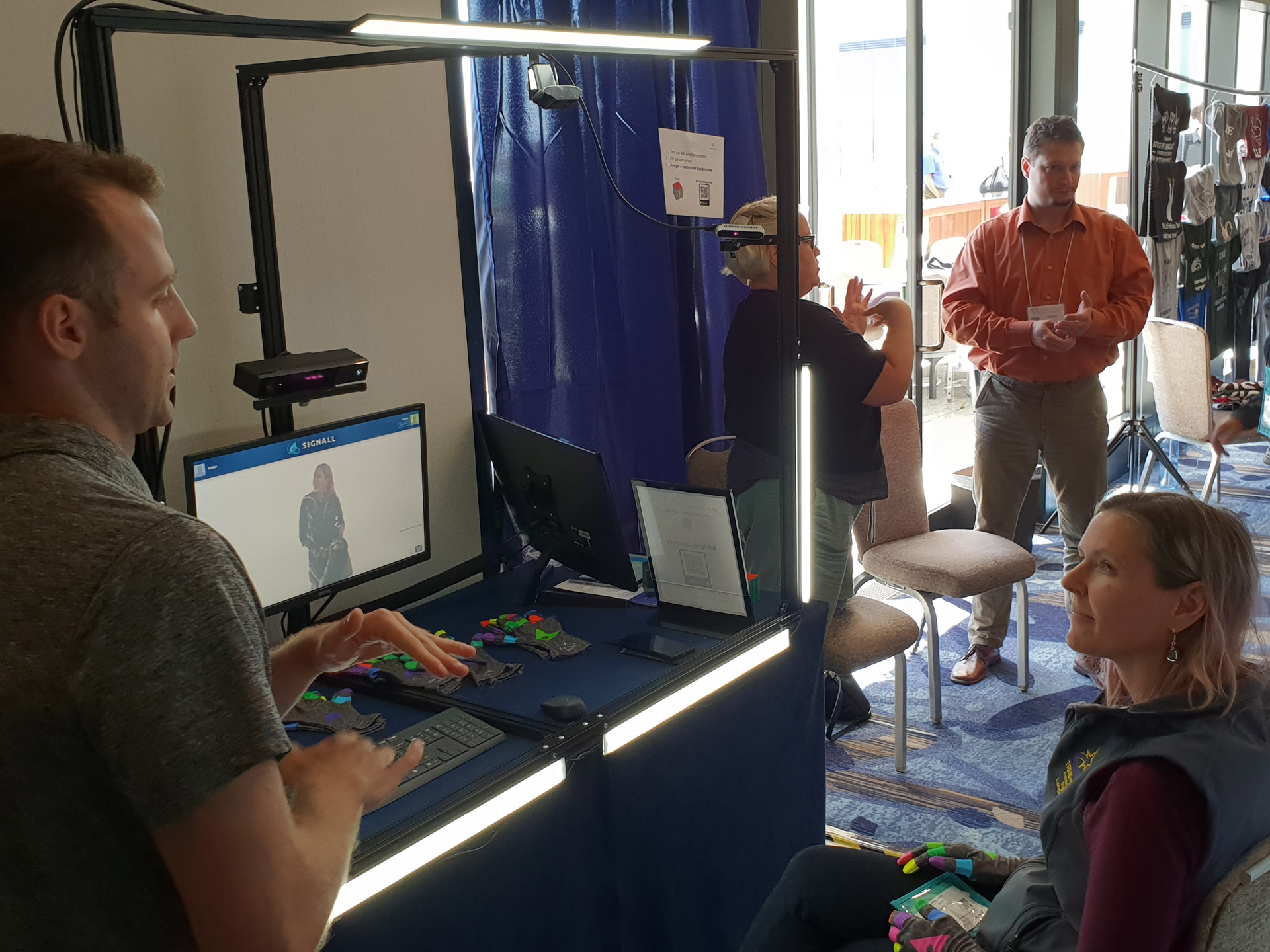 SignAll booth at an event. One person is practicing ASL with SignAll Learn system.