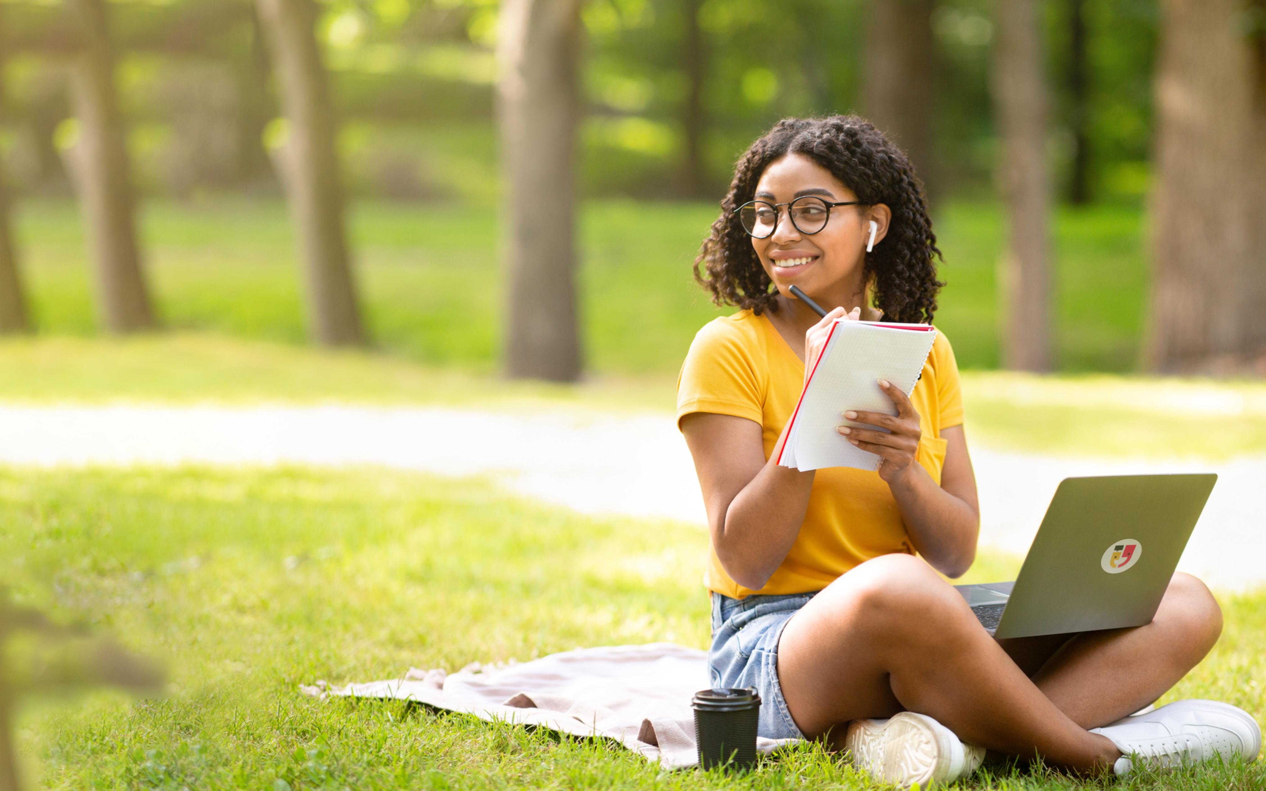 Uma jovem estudando com seu computador no parque