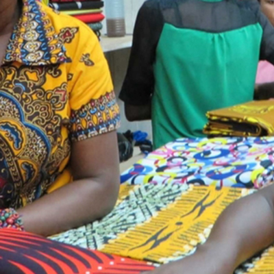 A woman selling fabrics at a market. Her dress and some of the fabric she's selling is a bright yellow color, close to the yellow used in the Water Compass color palette.