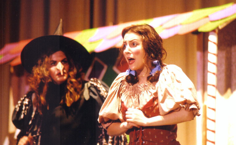 Oh man, get ready: Kelly is in pigtails and a little German dress, terrified look on her face, singing wildly, while a witch with scraggly red hair looks on, waiting to eat her. Three guesses which opera this was. (I'm not there to tell you, but it's Hansel and Gretel.)