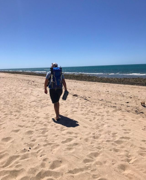 Walking on beach with backpack