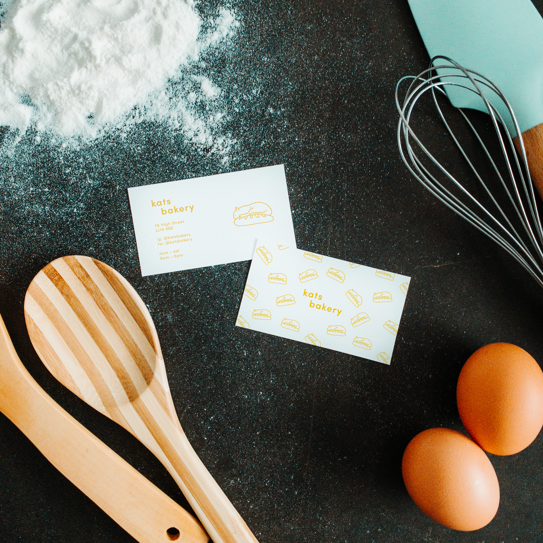 A messy bakery table with two business cards.