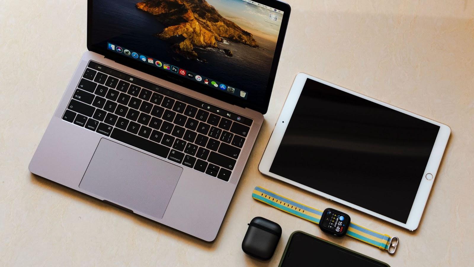 Matériel informatique et objets connectés vus du dessus, posés sur une table