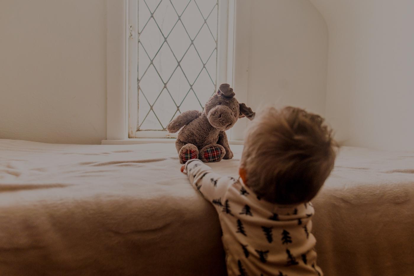 ein Kleinkind spielt mit seinem Kuscheltier