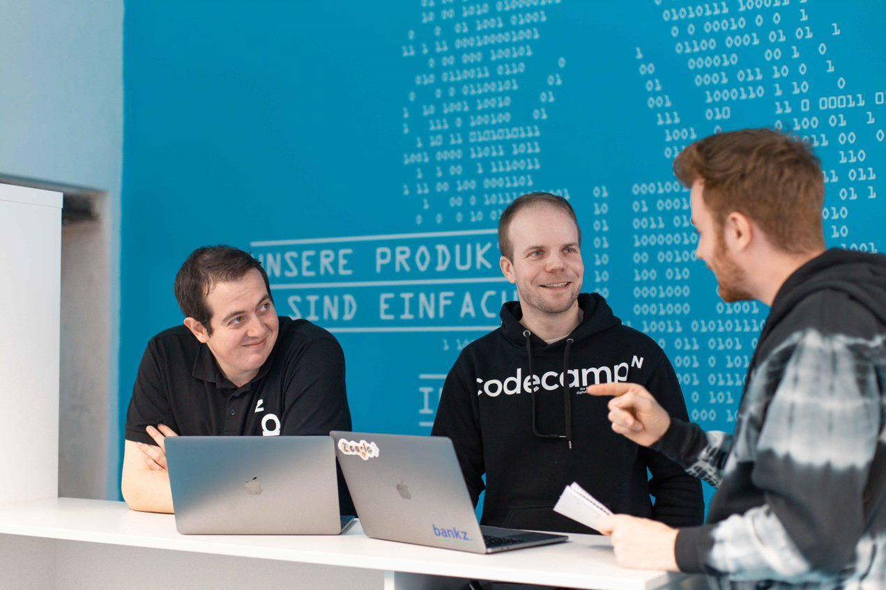 Vor einem Bildschirm mit Code, sitzt ein Mann und im Hintergrund sieht man weitere arbeitende lächelnde Personen