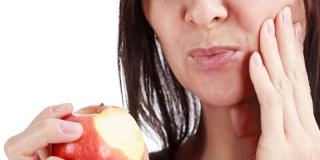 Photo of a woman biting into an apple and hurting her tooth