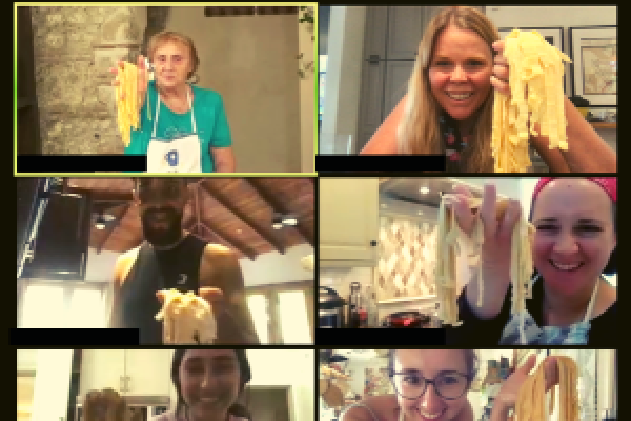 six people on zoom smiling and holding up noodles
