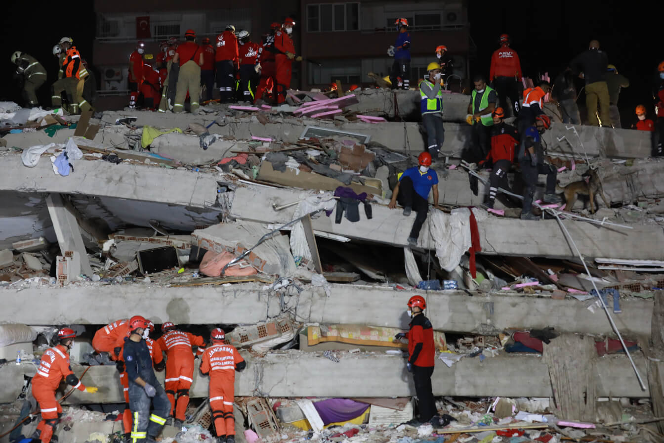 workers in masks and helmets digging through the rubble of a collapsed building in Turkey