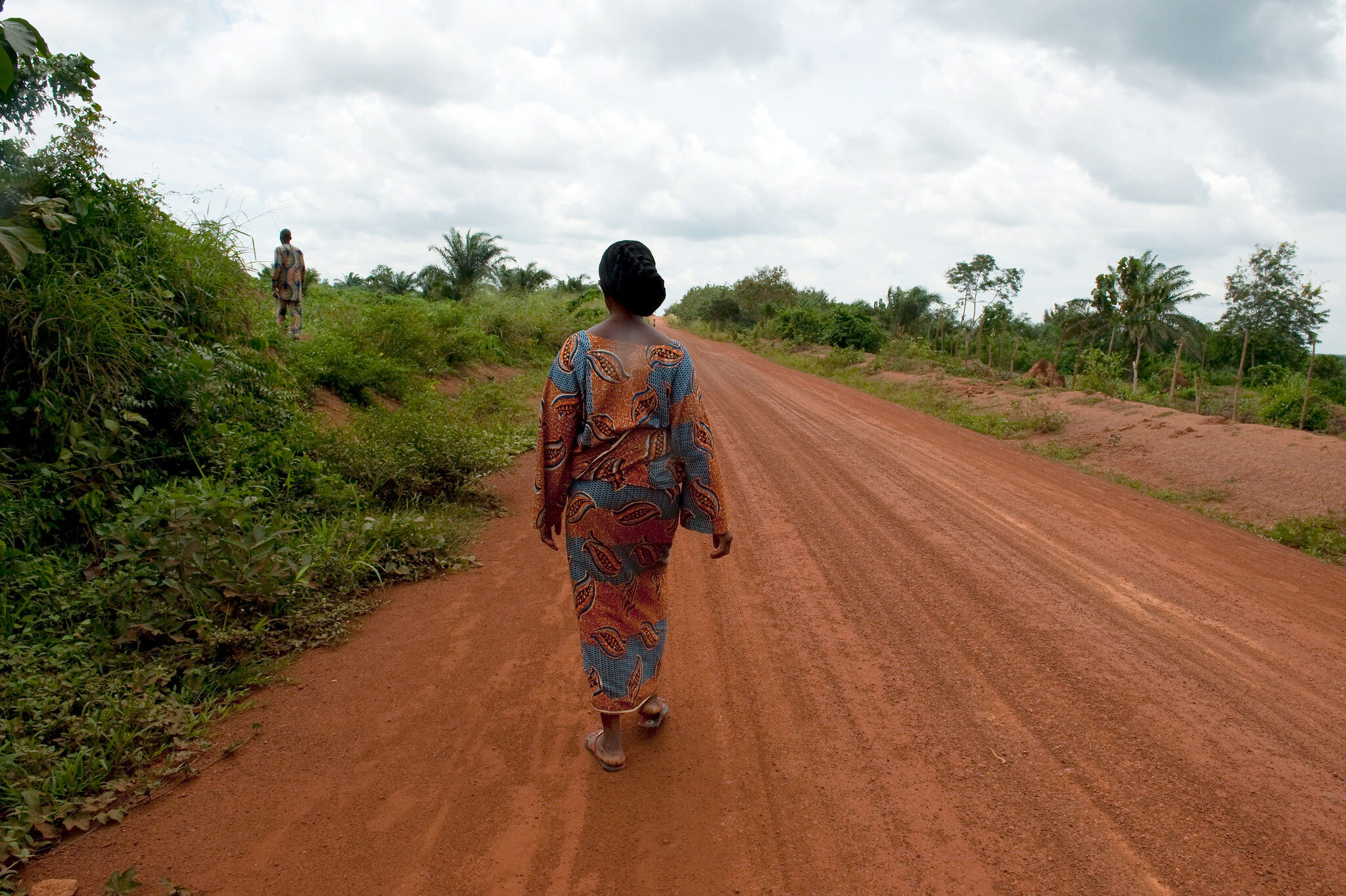 a woman in a dress and sandals walking down a dirt road