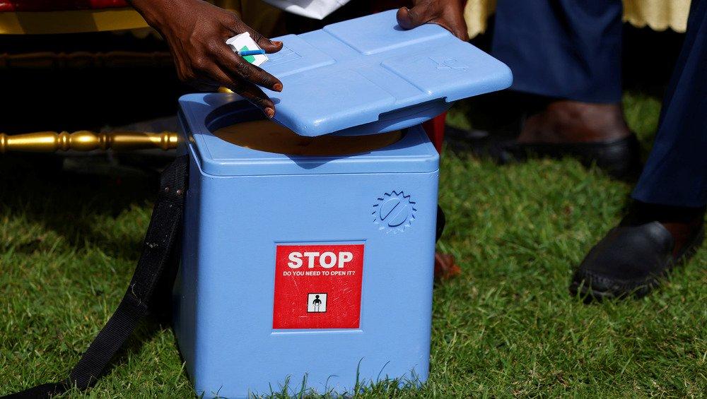 A health worker takes a dose of the coronavirus disease vaccine from an ice box in Dakar, Senegal 23 February, 2021. (Zohra Bensemra/REUTERS)