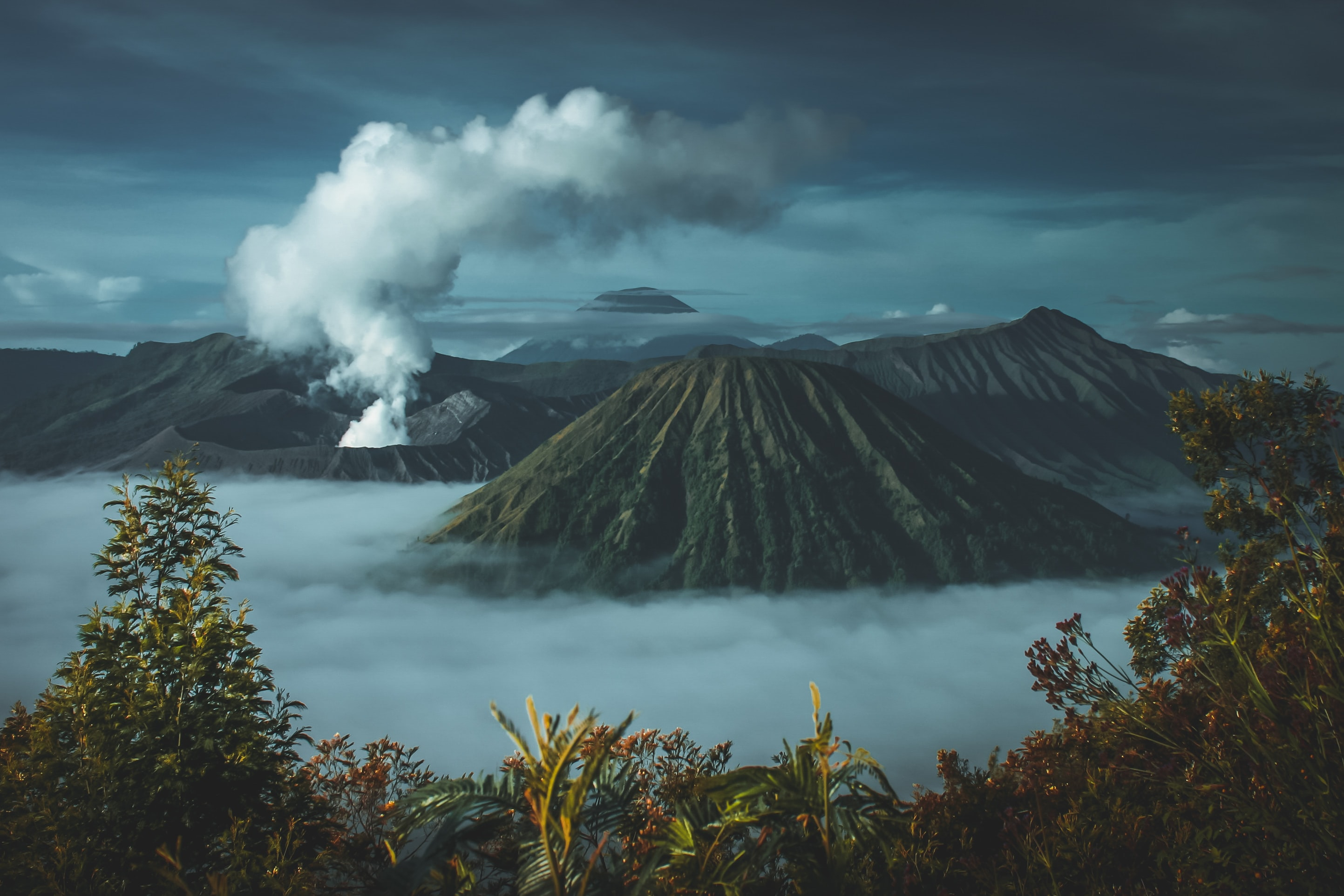 a volcano smoking in a tropical setting