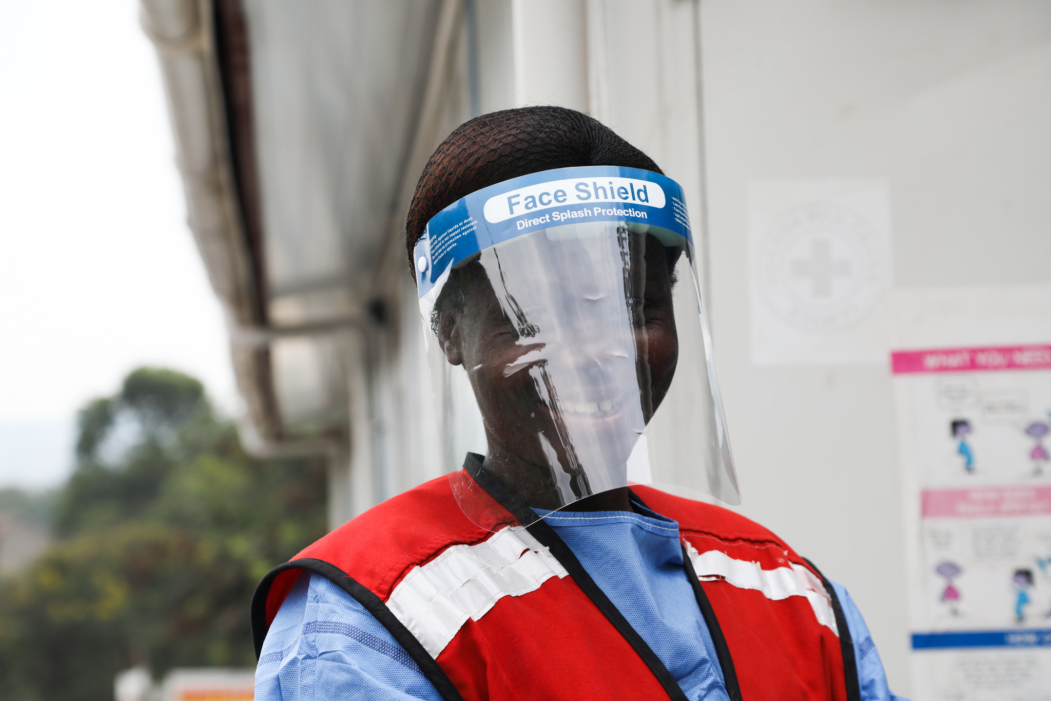 woman wearing a face shield and holding a digital thermometer