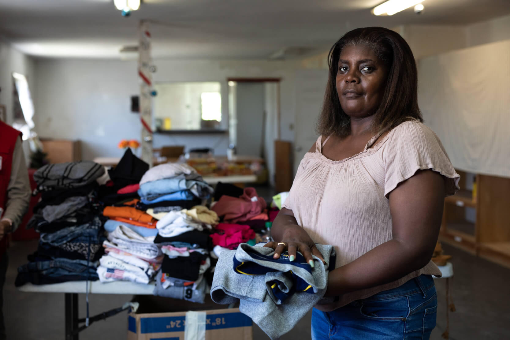 a woman folding clothes to prepare for a disaster