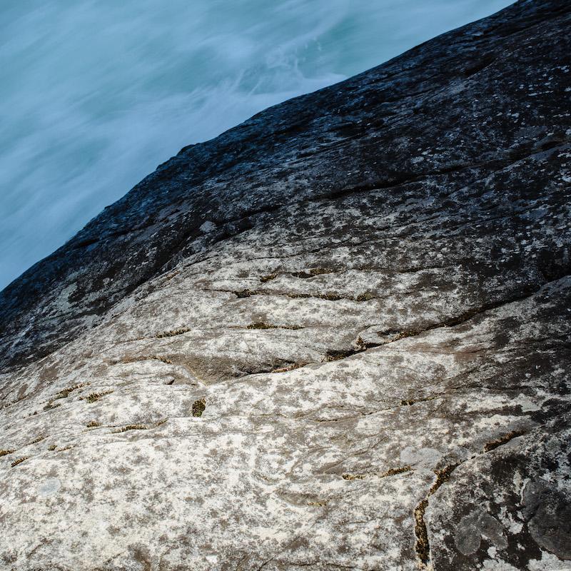 Rushing river below granite boulder