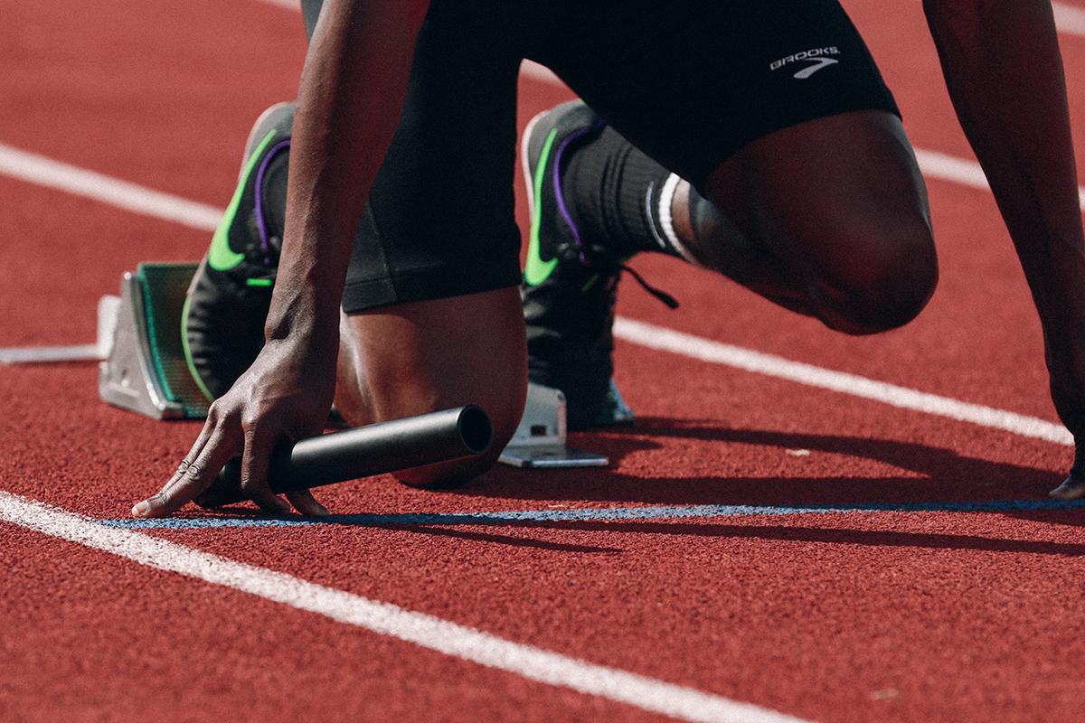 Sprinter im Startblock mit Staffelstab