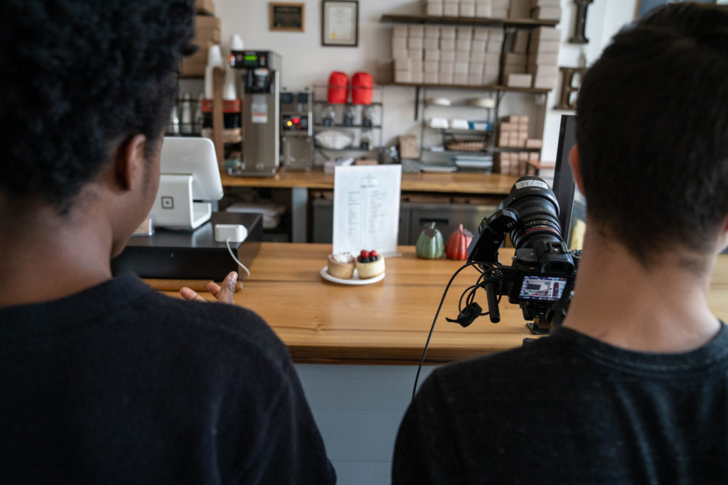 two students filming at a bakery with a counter with a piece of cake placed on it.