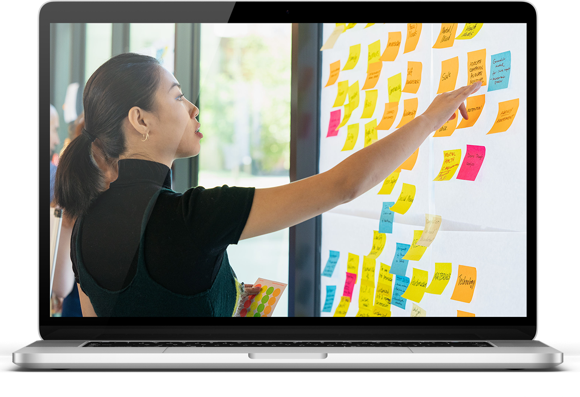 woman pointing at sticky notes on screen of macbook laptop