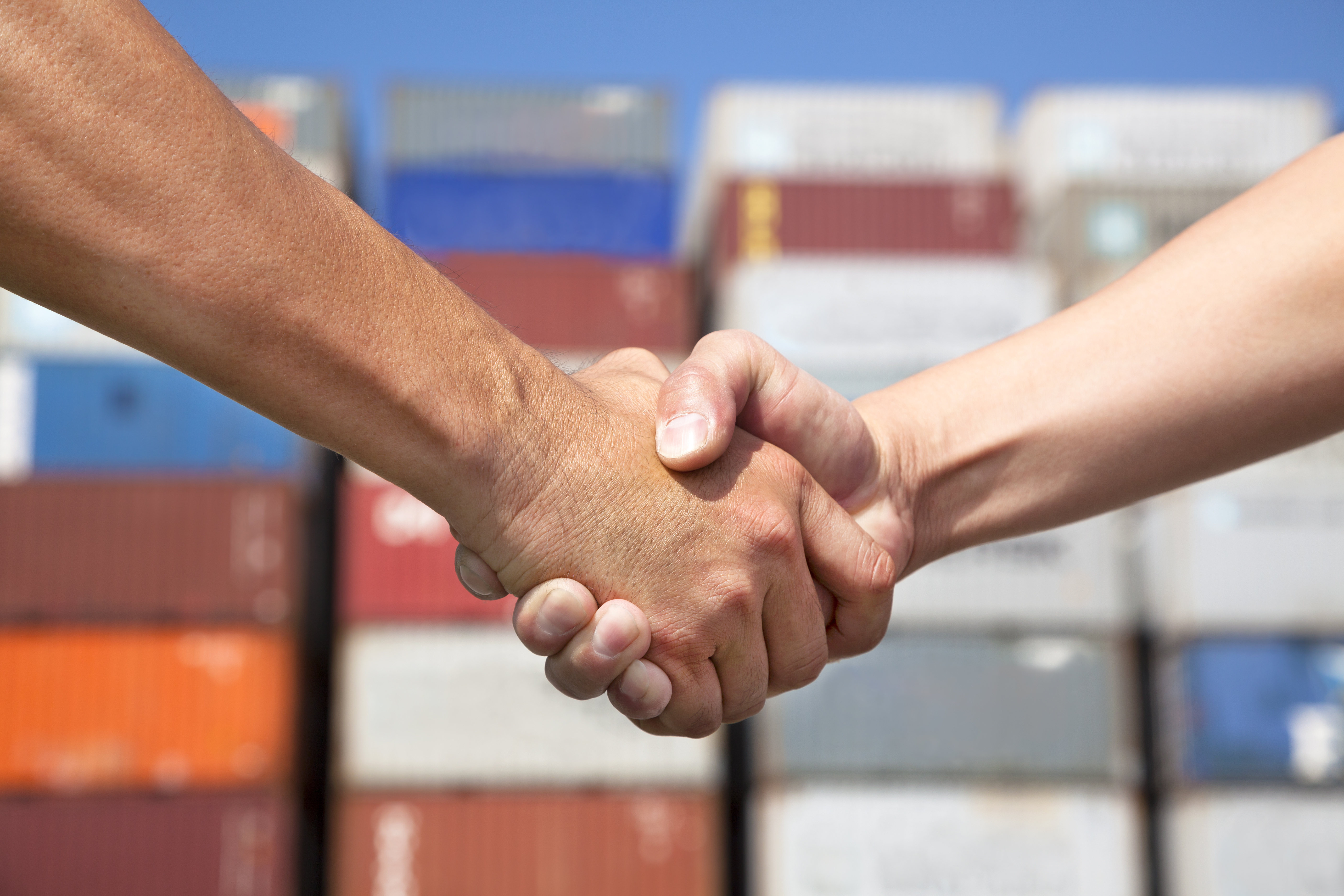 handshake in front of shipping containers