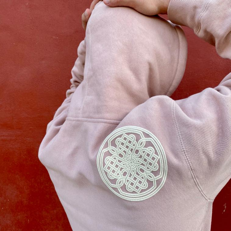 Puff print khachkar rosette on back of heavy pink hoodie